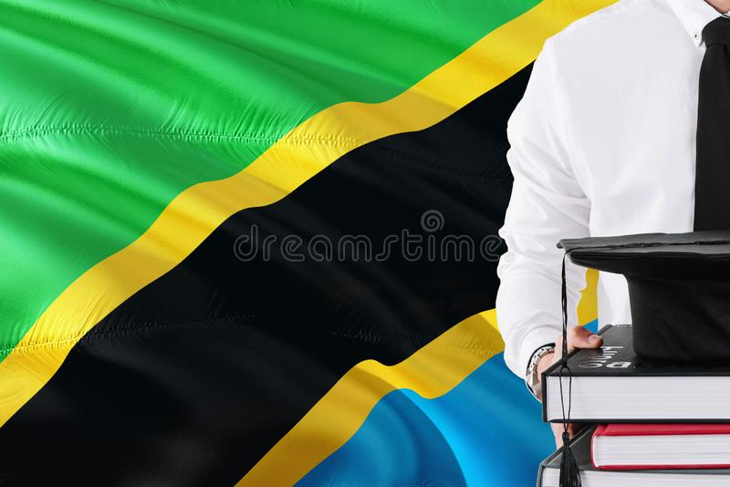 Successful Tanzanian student education concept. Holding books and graduation cap over Tanzania flag background.  stock photos