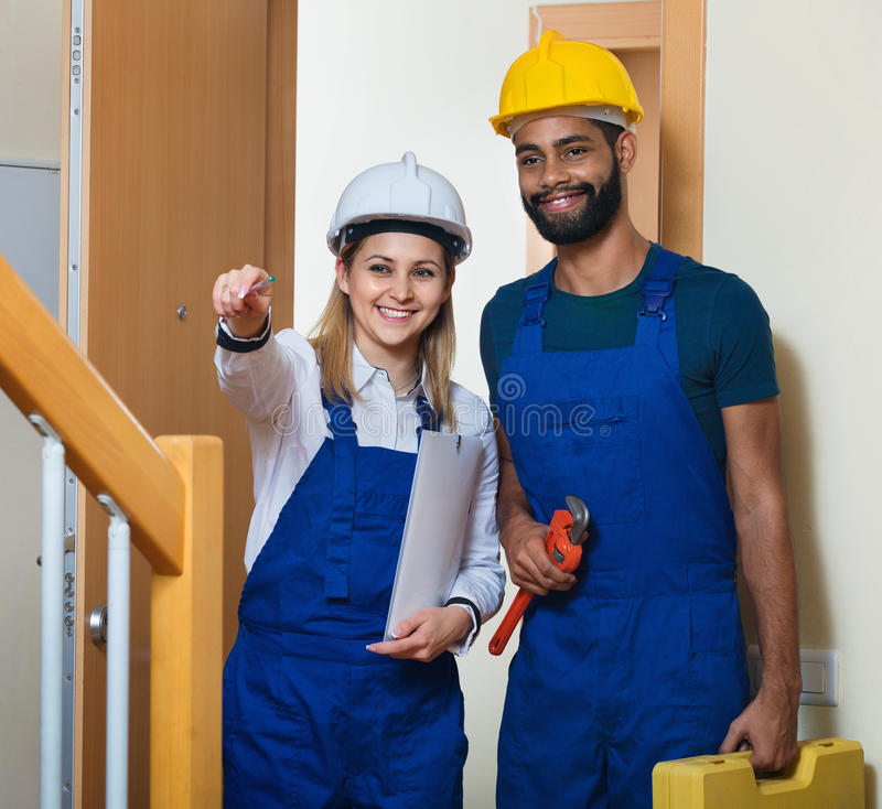 Successful team of builders standing at entrance. And smiling royalty free stock image