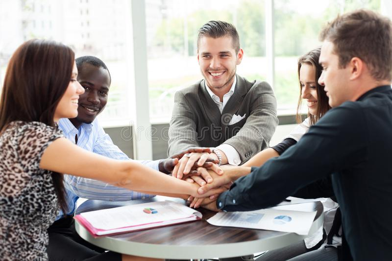 Successful team. Diverse group of business colleagues holding hands on top of one another in a symbol of unity while stock image