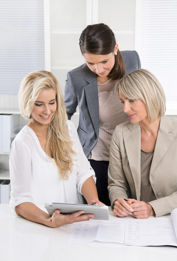 Successful team of female business people looking at tablet comp. Happy teamwork: three business women looking at tablet screen and documents royalty free stock photo