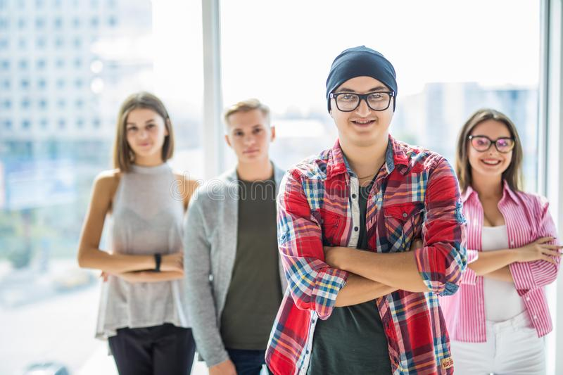 Successful team leader with a warm friendly smile standing with folded arms in front of the friends people royalty free stock photo