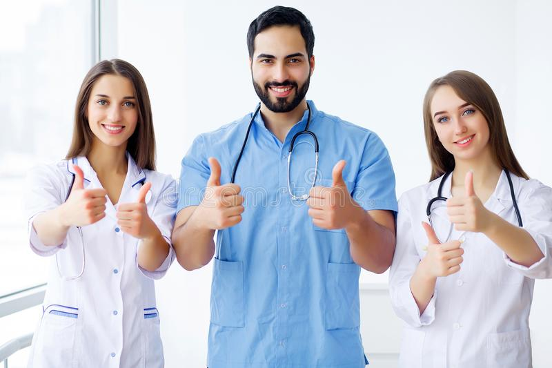 Successful team of medical doctors are looking at camera and smiling while standing in hospital royalty free stock images