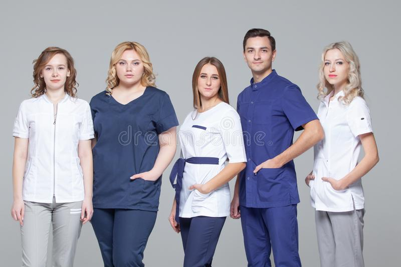 Successful team of medical doctors are looking at camera while standing on grey background stock images
