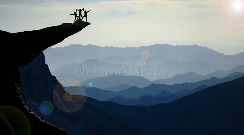 Successful team on rock ledge royalty free stock photo