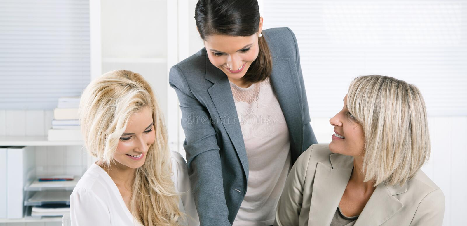 Successful team of well educated businesswoman sitting at desk w stock image