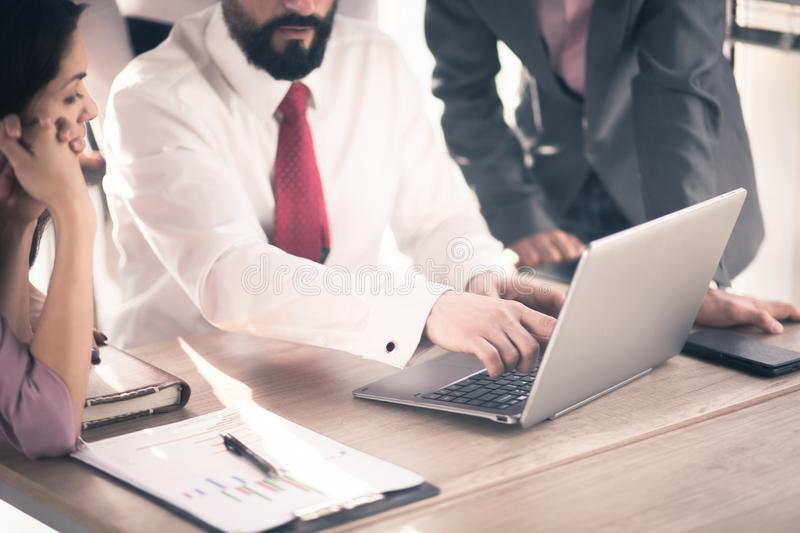Successful team at work. Team lead sitting at laptop and showing data to managers on laptop in luxury office royalty free stock images