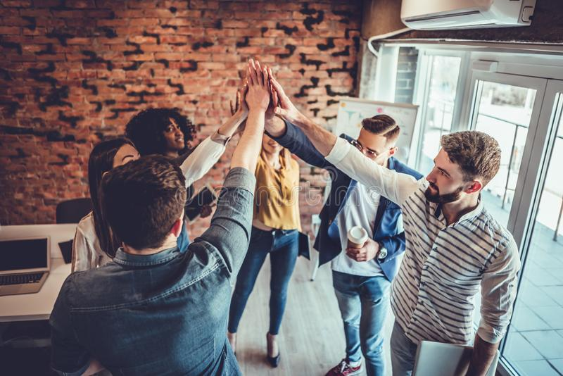 Successful team of young professionals celebrating achievement in work project giving high-five to each other in office stock images
