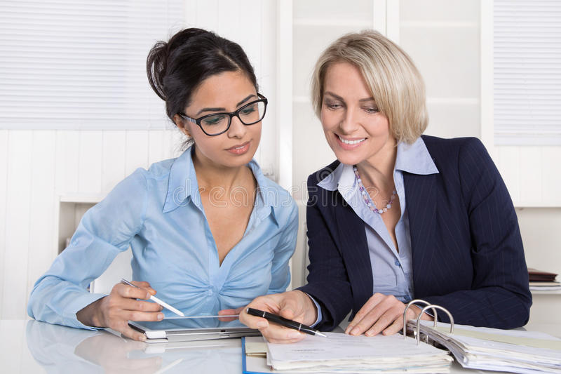 Successful teamwork under businesswoman at desk. Teamwork with trainee and mature boss at desk stock photo