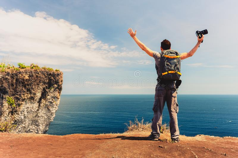 Successful traveler man photographer standing with raised hands on the top mountain cliff on background nature landscape. Happy travel man backpacker with camera stock photos