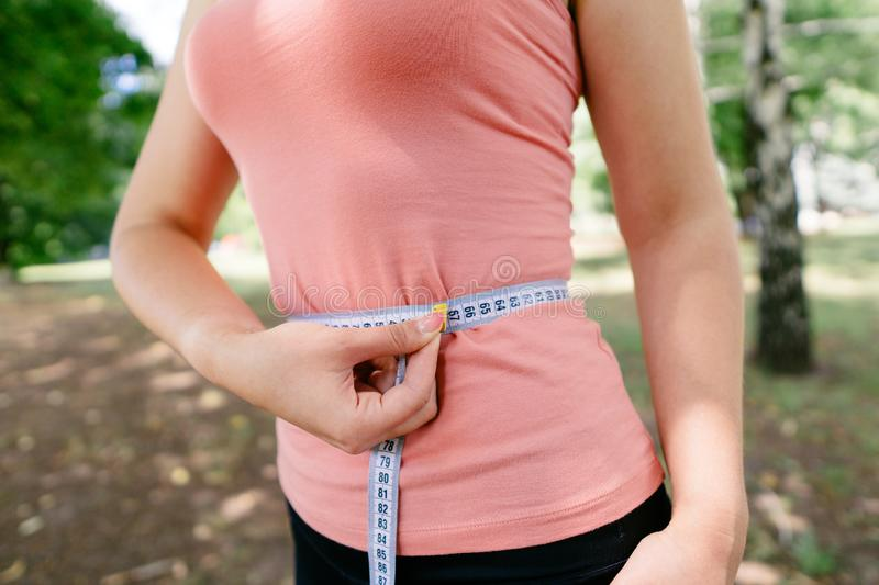 Woman with slim body measuring her waistline. Successful weight loss, diet, motivation and healthy lifestyle. Woman with perfect slim body measuring her royalty free stock photo