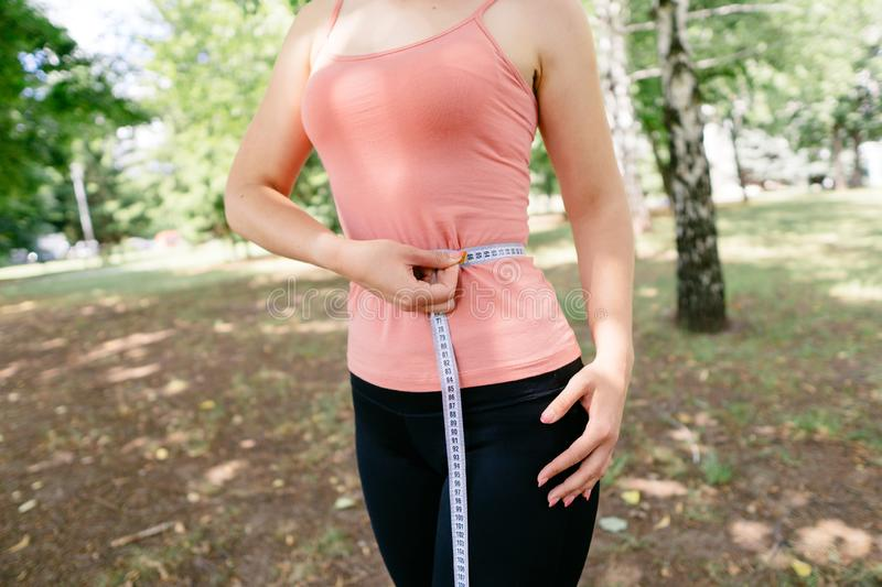 Woman with slim body measuring her waistline. Successful weight loss, diet, motivation and healthy lifestyle. Woman with perfect slim body measuring her stock photography