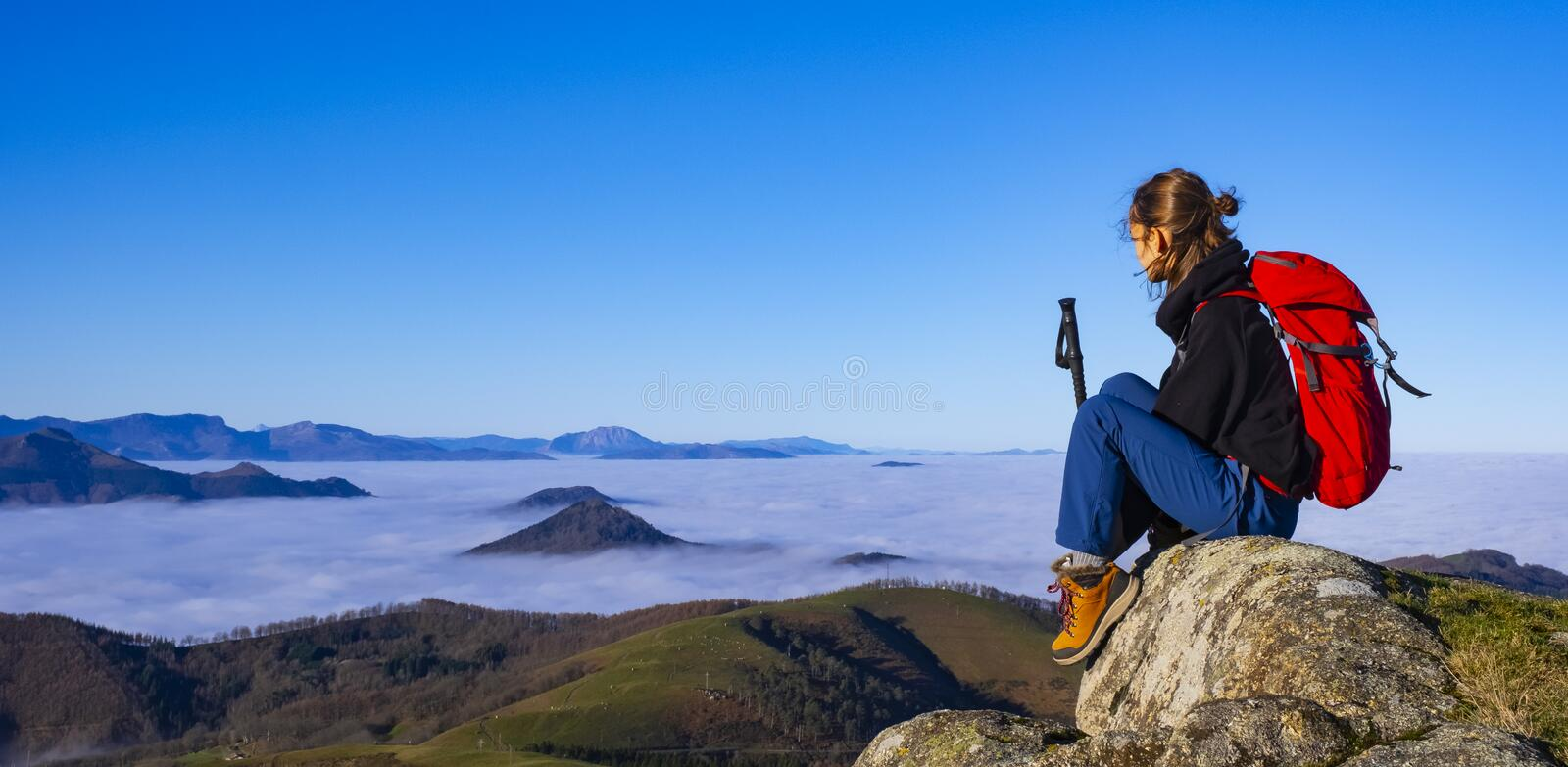 Successful woman backpacker enjoy the view on mountain peak stock photography
