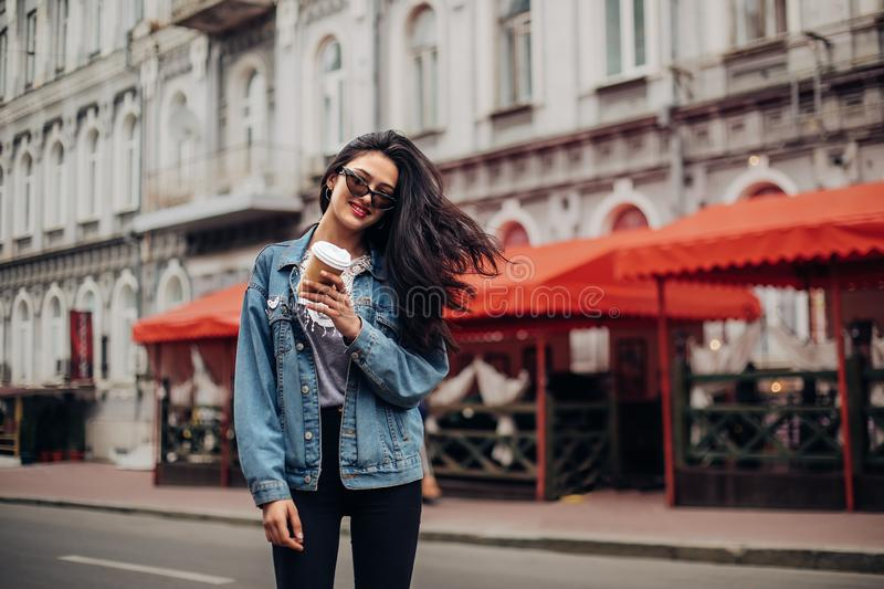 Successful woman, blogger. young stylish girl holds coffee to go. Wearing fashionable glasses and denim jacket. Hipster outfit stock photography