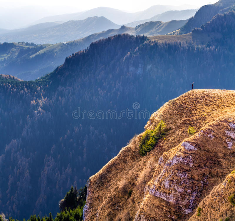 Successful woman standing on the edge of a cliff,reaching her goal. Courageous woman standing on the edge of a cliff,on the high mountains,feeling powerful stock image