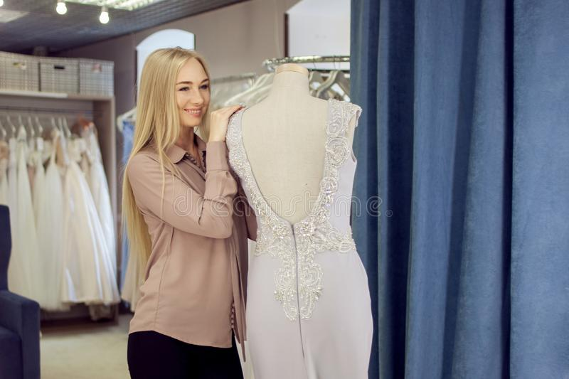 . Successful woman entrepreneur. Beautiful blonde in boutique of wedding and evening fashion stock photos