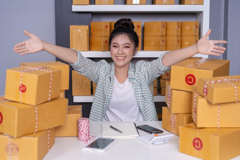 Successful woman entrepreneur with parcel boxes in her own job s. Successful young woman entrepreneur with parcel boxes in her own job shopping online business stock photos