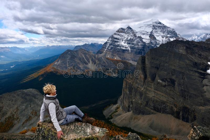 Successful woman hiker sitting on mountain top enjoying view of mountain valley with yellow larch trees from above. stock photo