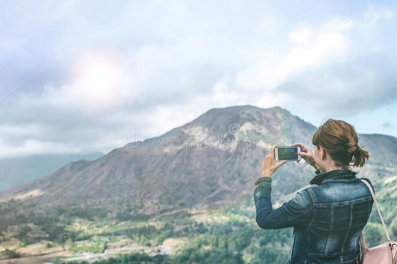 Successful woman hiker taking picture with smartphone at cliff edge on mountain top. Bali island. stock photo