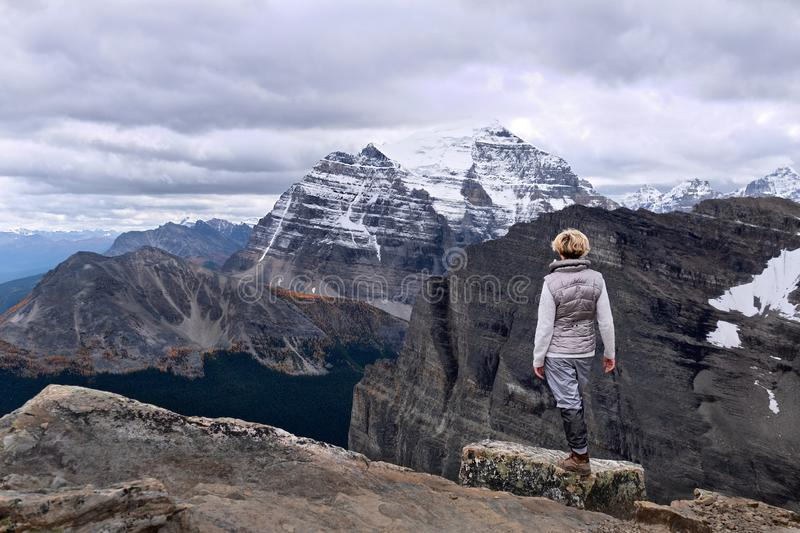 Successful woman on mountain top looking happy and confident. royalty free stock photo