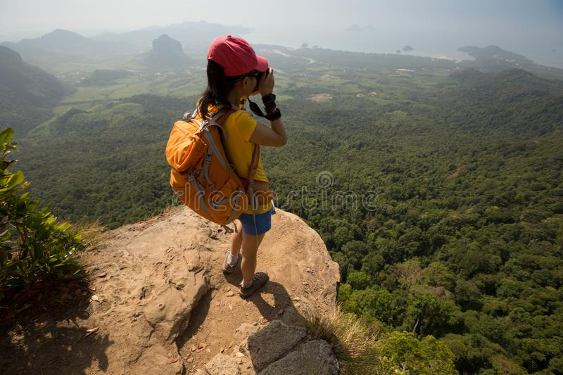 Woman photographer taking photo on mountain peak cliff royalty free stock photo