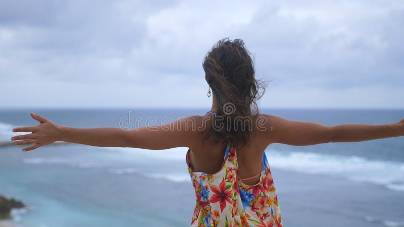 Successful young woman reached top of moutain. Girl rise her hands in the air. royalty free stock photo