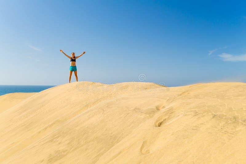 Successful woman running on sand desert dunes stock photos