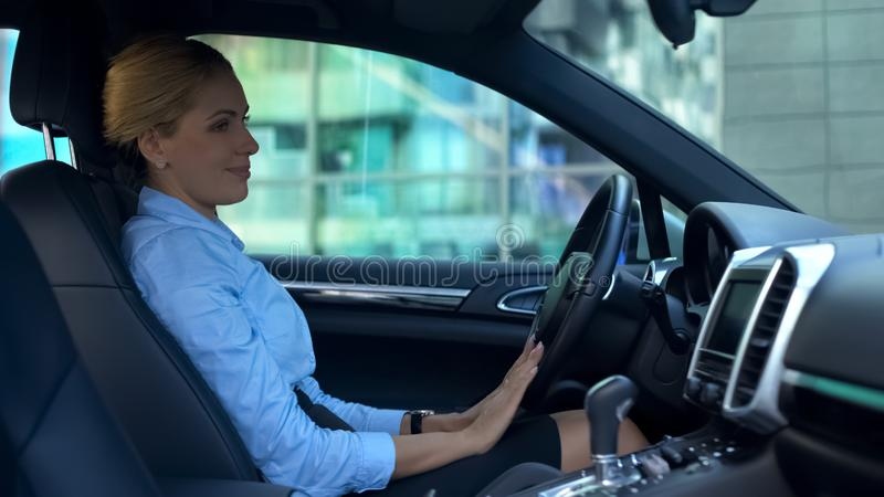 Successful woman stroking car with love, purchase of luxury auto, happy buyer stock photography