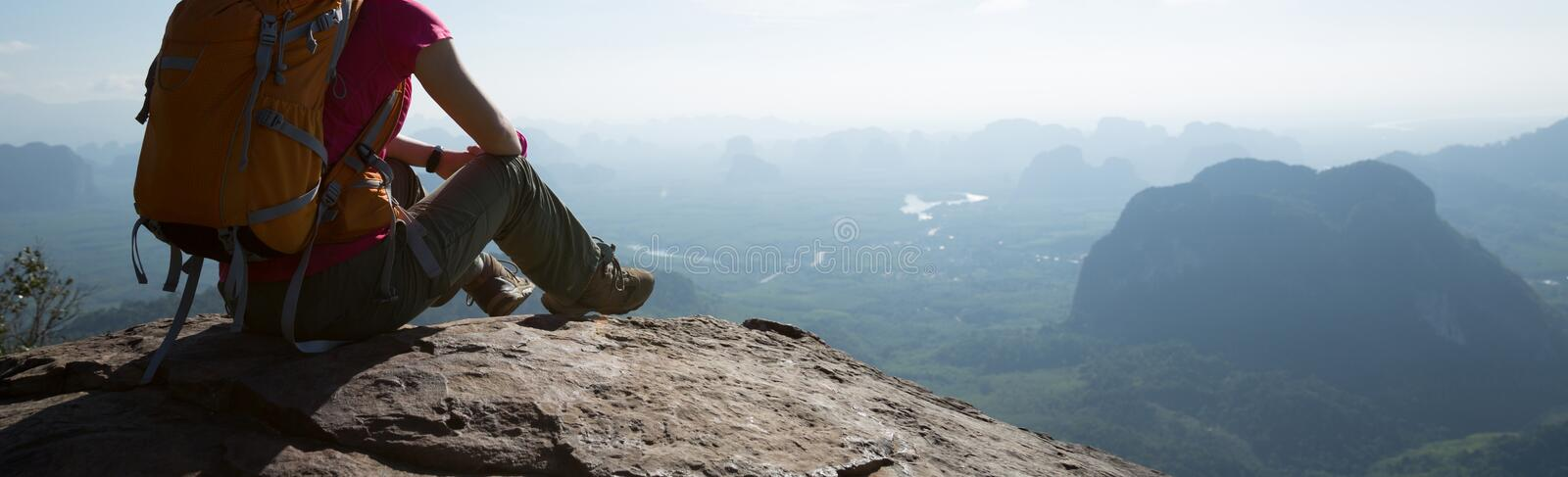 Woman traveler sitting on mountain peak cliff edge. Successful woman traveler sitting on mountain peak cliff edge stock images