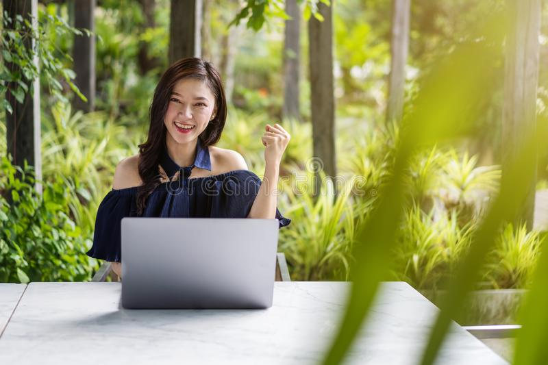 Successful woman using laptop with arms raised royalty free stock photography