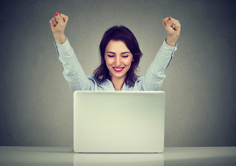 Successful woman winner with arms raised looking at laptop royalty free stock photography
