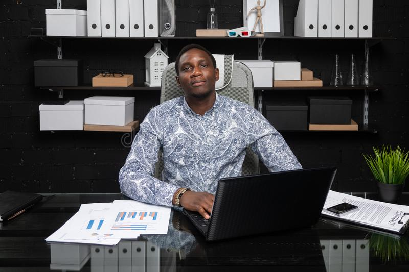 Portrait of Beautiful young African American businessman working with documents and laptop in office. Successful young African man sits at his Desk in office and royalty free stock photography