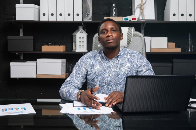 Portrait of Beautiful young African American businessman working with documents and laptop in office. Successful young African man sits at his Desk in office and royalty free stock photo