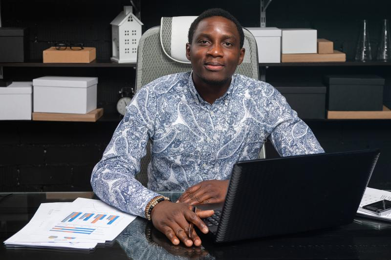 Portrait of Beautiful young African American businessman working with documents and laptop in office. Successful young African man sits at his Desk in office and stock photo