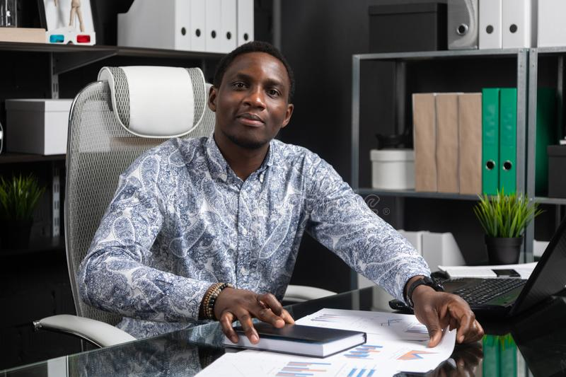 Portrait of Beautiful young African American businessman working with documents and laptop in office. Successful young African man sits at his Desk in office and royalty free stock image