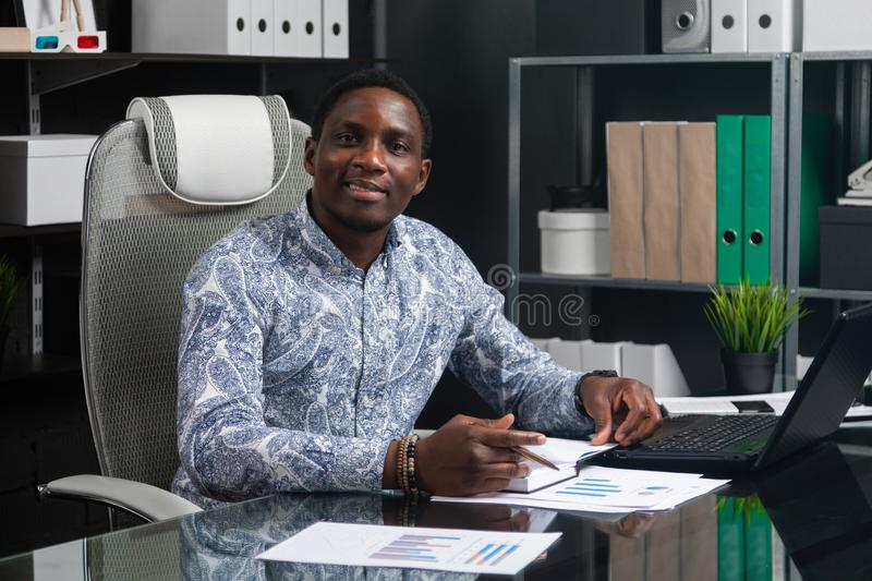 Portrait of Beautiful young African American businessman working with documents and laptop in office. Successful young African man sits at his Desk in office and stock photography