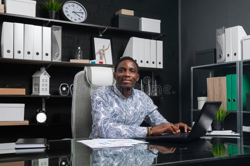 Portrait of Beautiful young African American businessman working with documents and laptop in office. Successful young African man sits at his Desk in office and royalty free stock photos