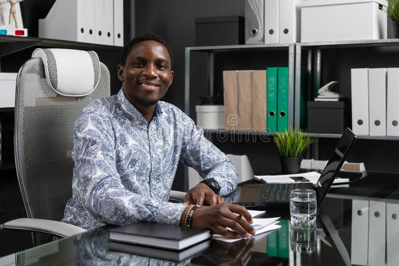 Portrait of Beautiful young African American businessman working with documents and laptop in office. Successful young African man sits at his Desk in office and stock photos