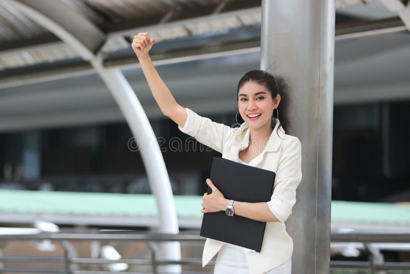 Successful young Asian business woman with binder raising arms. stock photos