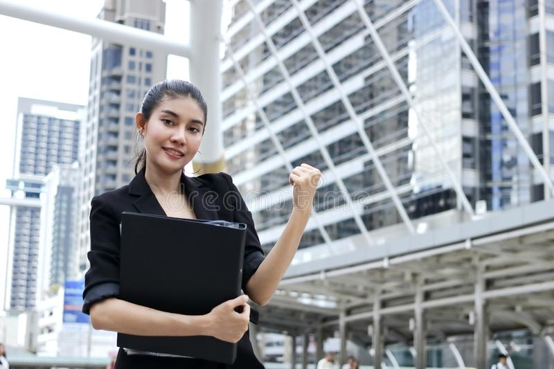 Successful young Asian business woman with binder raising arms stock images