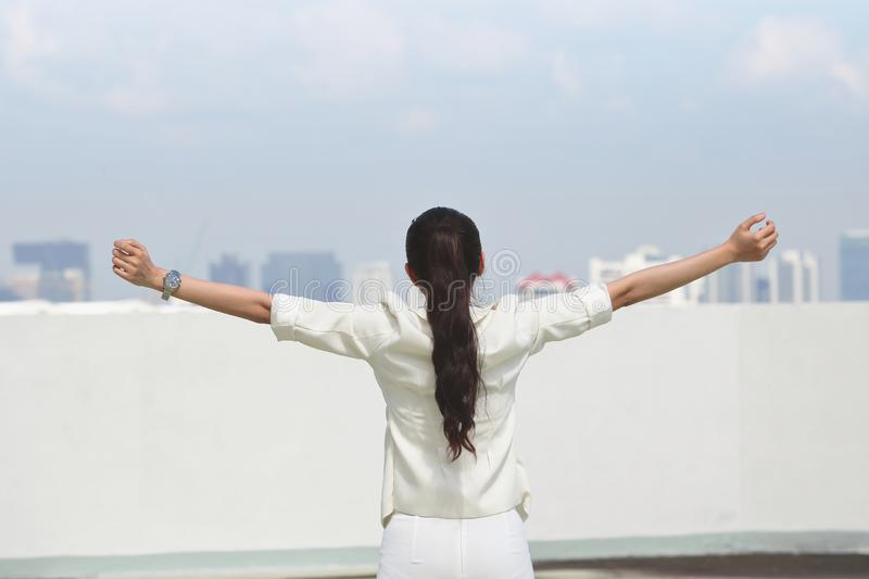Successful young Asian business woman raising arms with skyscrapers background.  royalty free stock photography