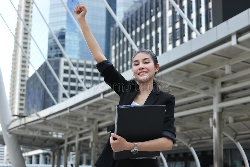 Successful young Asian business woman raising hands with modern buildings city background. stock photos