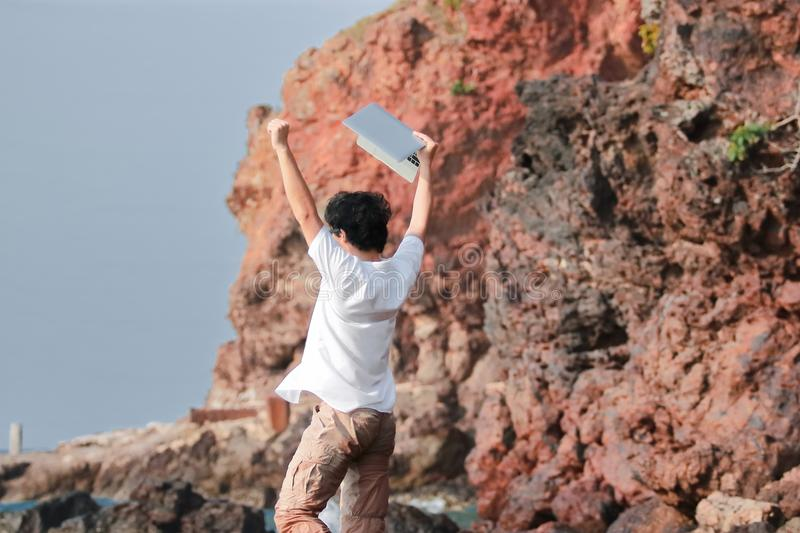 Successful young Asian man with laptop raising fist and celebrating after work complete at sea shore stock photography