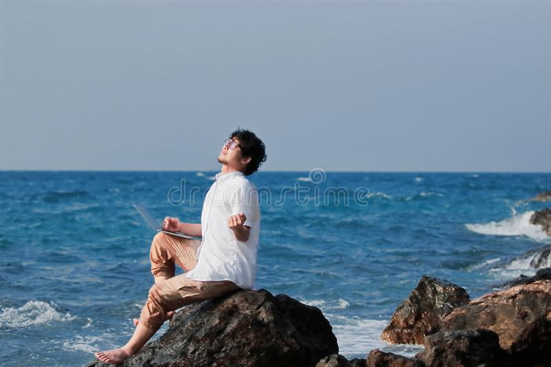 Successful young Asian man with laptop raising hands at sea shore stock photography