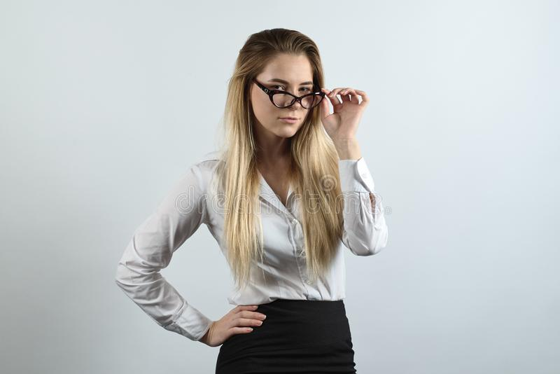 successful young attractive businesswoman with long hair and glasses posing for a portrait dressed in a stack of business style. stock photo