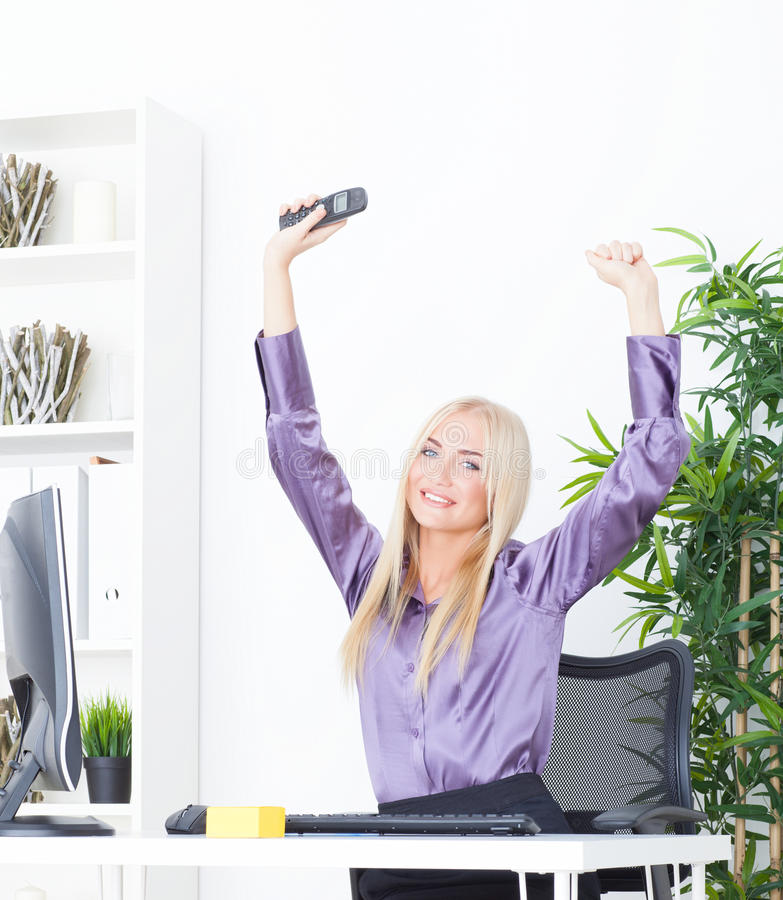 Successful young blonde businesswoman, victory gesture, hands up, smiling at office. Successful young businesswoman, victory gesture, hands up, smiling at office royalty free stock photo