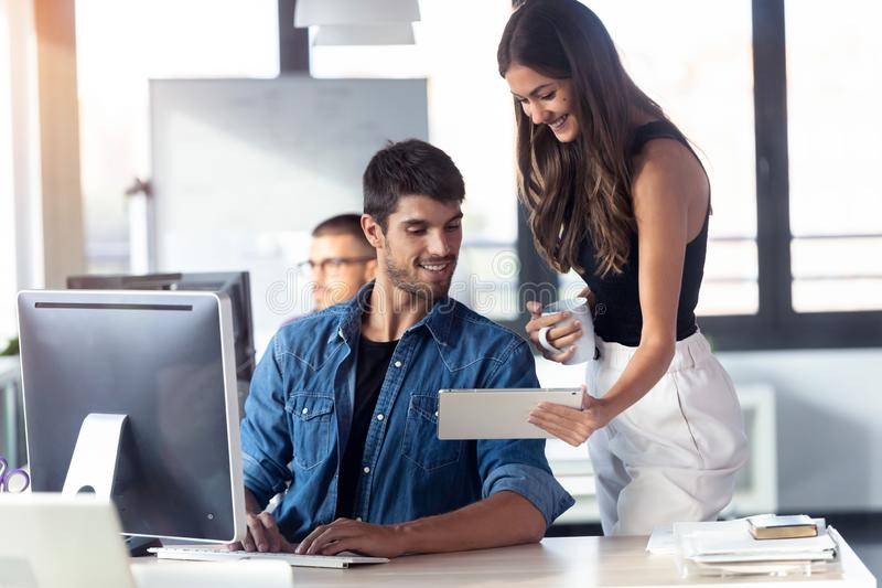 Successful young business couple working together with digital tablet in the modern startup office stock images