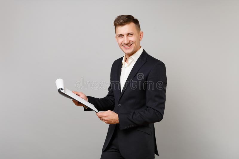 Successful young business man in classic black suit, shirt holding clipboard with papers document isolated on grey stock photography