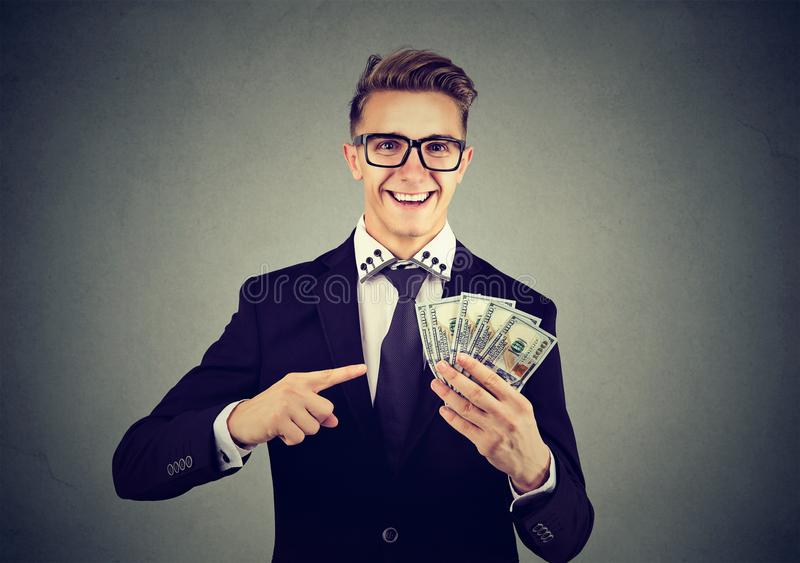 Successful young business man holding money dollar bills in hand royalty free stock image