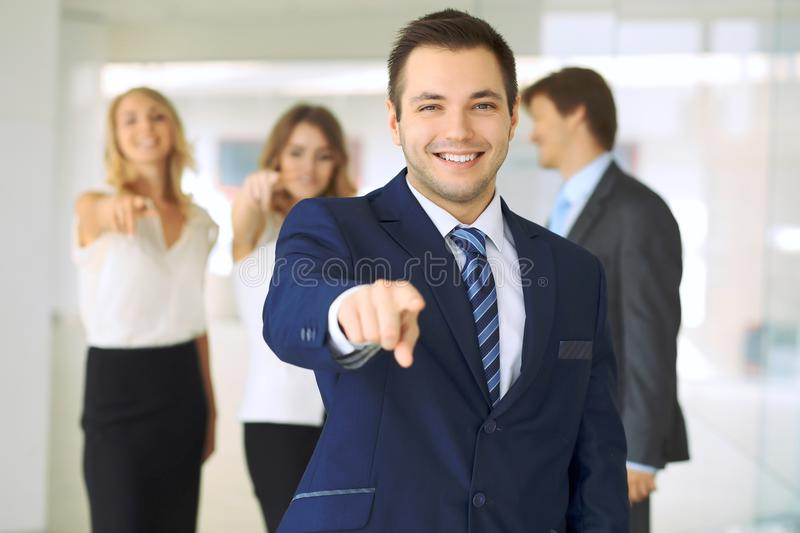Successful young business people showing thumbs up sign while standing in office interier.  stock photography