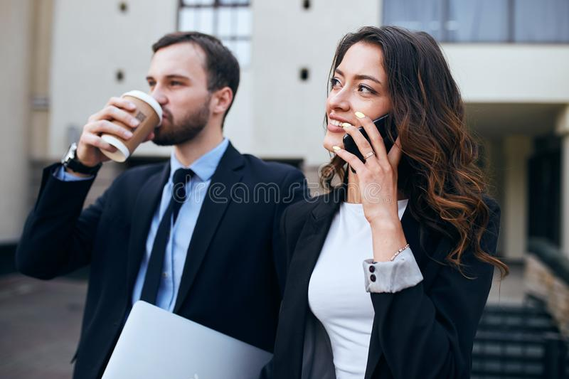 Successful young business people talking with smart phone and drinking tea stock images
